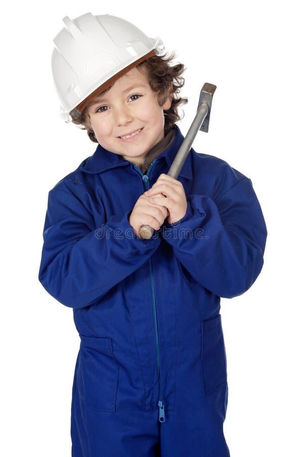 El muchacho adorable vistió al trabajador en un martillo y un casco imágenes de archivo libres de regalías