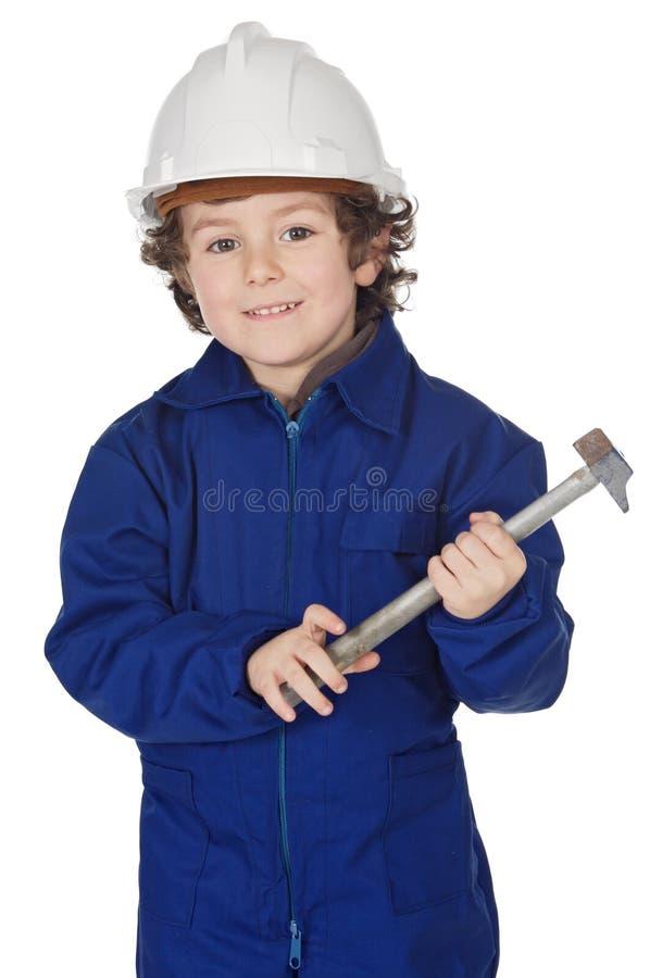 El muchacho adorable vistió al trabajador en un martillo y un casco imagen de archivo libre de regalías