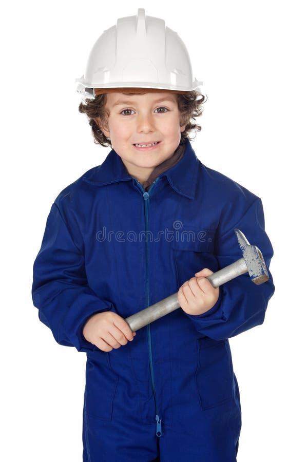 El muchacho adorable vistió al trabajador en un martillo y un casco foto de archivo