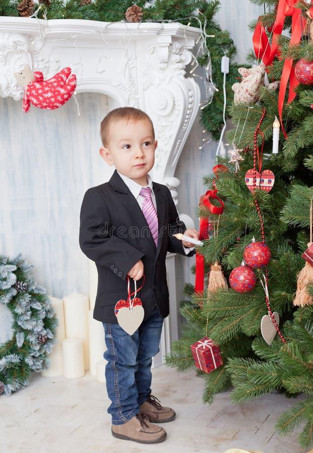 El muchacho adorna un árbol de navidad fotos de archivo libres de regalías