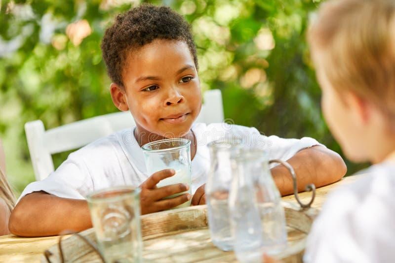 El muchacho africano est? bebiendo un vidrio de leche imagen de archivo