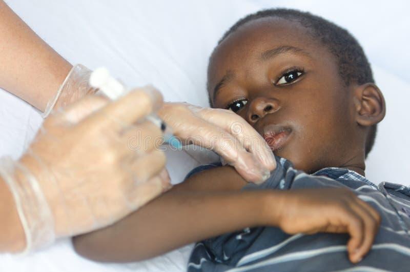 El muchacho africano triste está preocupado de conseguir una inyección para su salud como vacunación imagenes de archivo