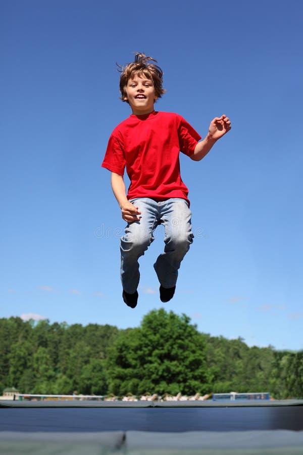 El muchacho alegre salta en el trampolín
