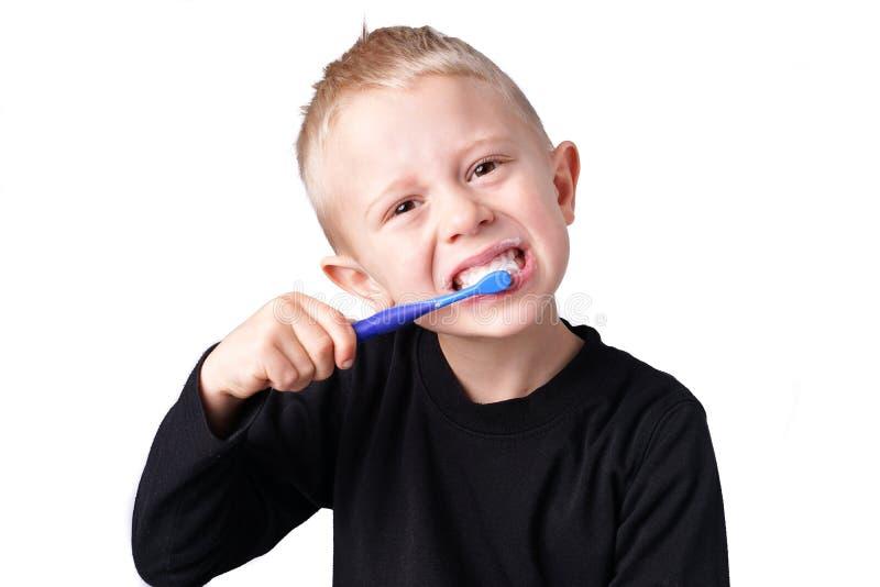 El muchacho aplica sus dientes con brocha imagenes de archivo