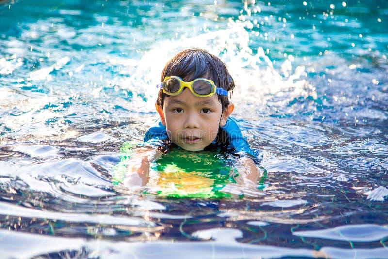 El muchacho aprende nadar en la piscina imagen de archivo