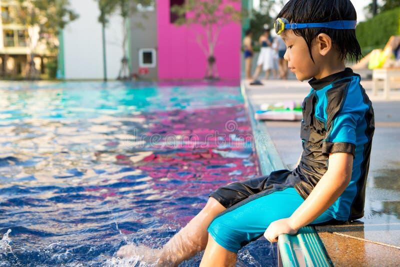 El muchacho aprende nadar en la piscina fotografía de archivo