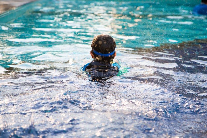 El muchacho aprende nadar en la piscina imagenes de archivo
