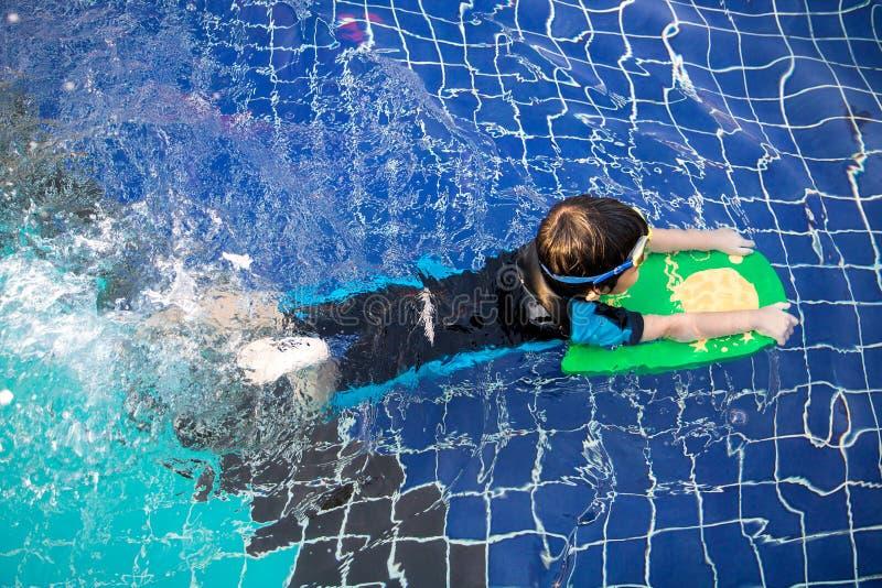 El muchacho aprende nadar en la piscina fotos de archivo