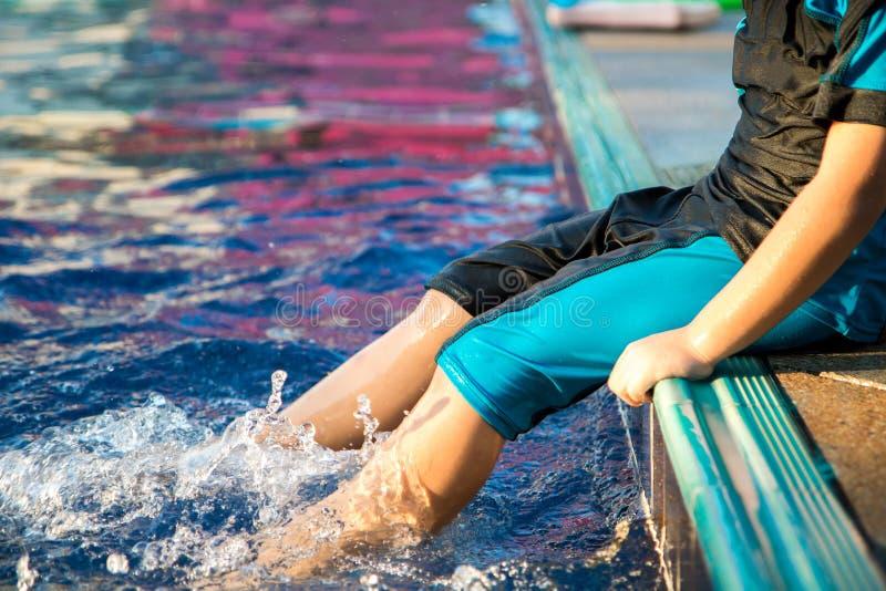 El muchacho aprende nadar en la piscina fotografía de archivo libre de regalías