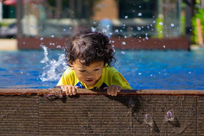 El muchacho asiático del niño aprende la natación en una piscina fotos de archivo libres de regalías