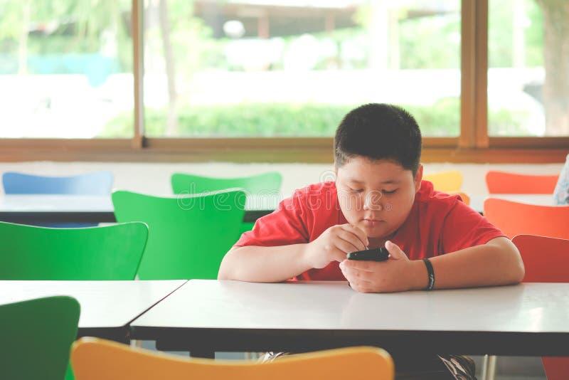 El muchacho asiático del niño es adictivo jugando la tableta y los teléfonos móviles imágenes de archivo libres de regalías