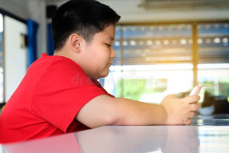 El muchacho asiático del niño es adictivo jugando la tableta y los teléfonos móviles imagenes de archivo