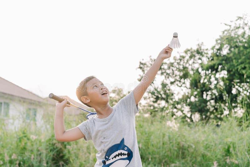 El muchacho asiático del niño está jugando al bádminton al aire libre en puesta del sol imagen de archivo libre de regalías