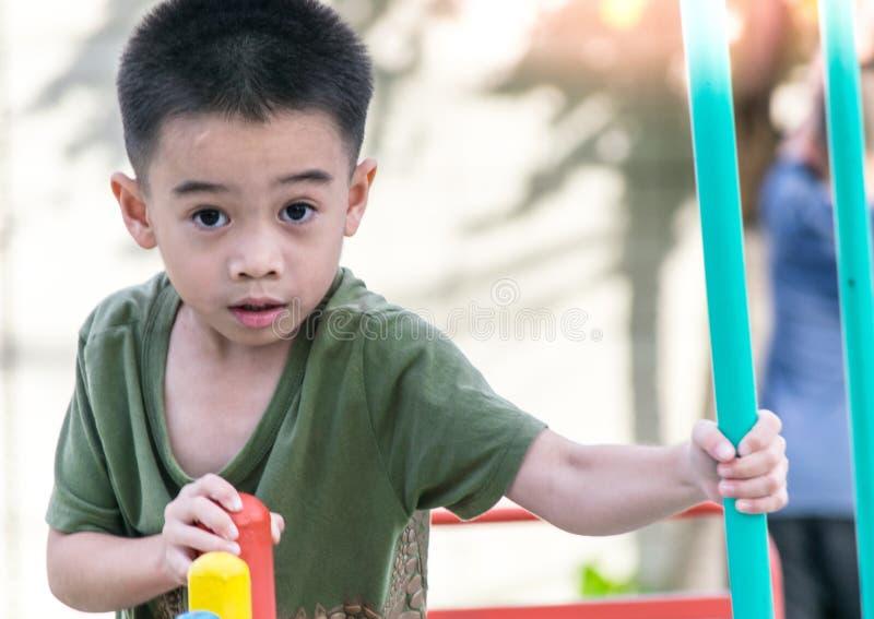 El muchacho asiático está jugando un patio en el pueblo borroso del backgroud del árbol de divertido fotografía de archivo libre de regalías