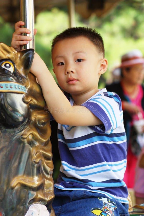 El muchacho asiático está librando el caballo imagen de archivo libre de regalías