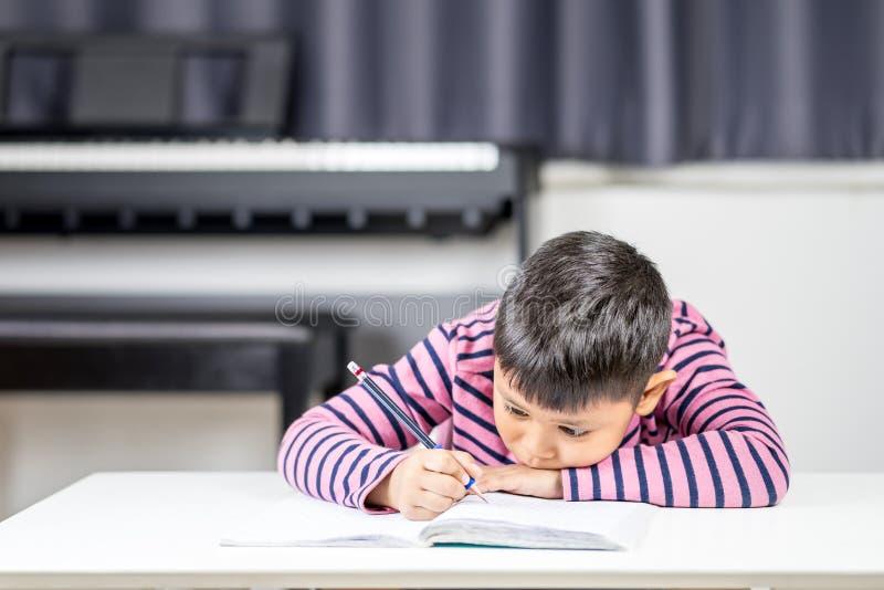 El muchacho asiático joven cansado escribe en el cuaderno por el lápiz en el ro imagen de archivo libre de regalías