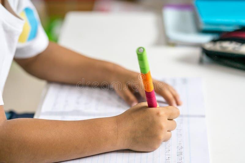 El muchacho asiático joven escribe en el cuaderno por el lápiz en el cuarto fotografía de archivo libre de regalías