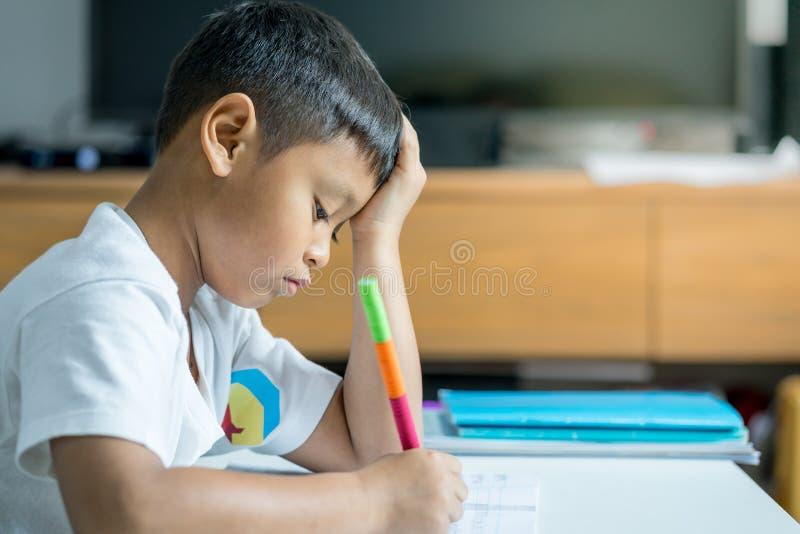 El muchacho asiático joven escribe en el cuaderno por el lápiz en el cuarto foto de archivo libre de regalías