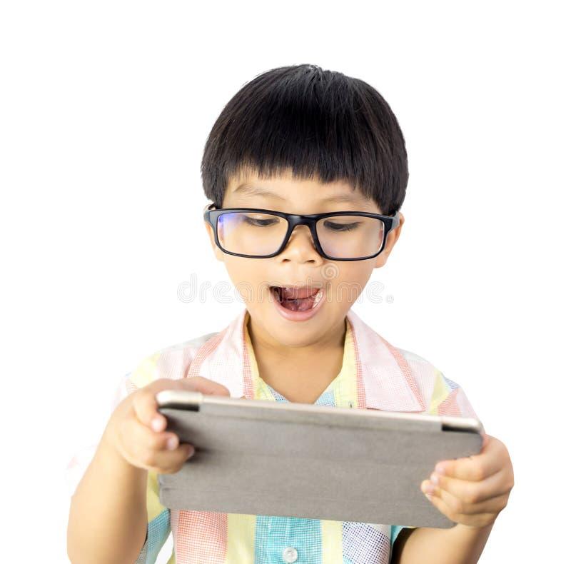 El muchacho asiático Nerdy es asombrosamente en la tableta aislada imagen de archivo libre de regalías
