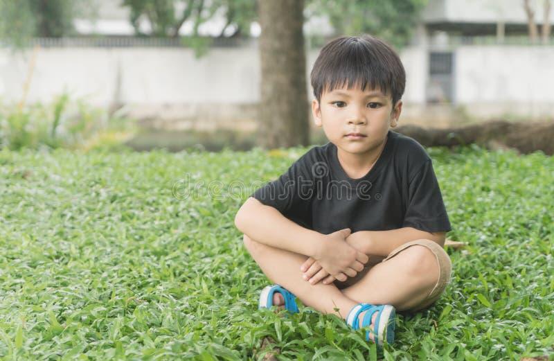 El muchacho asiático soñador se está sentando en la hierba en el parque imagen de archivo libre de regalías