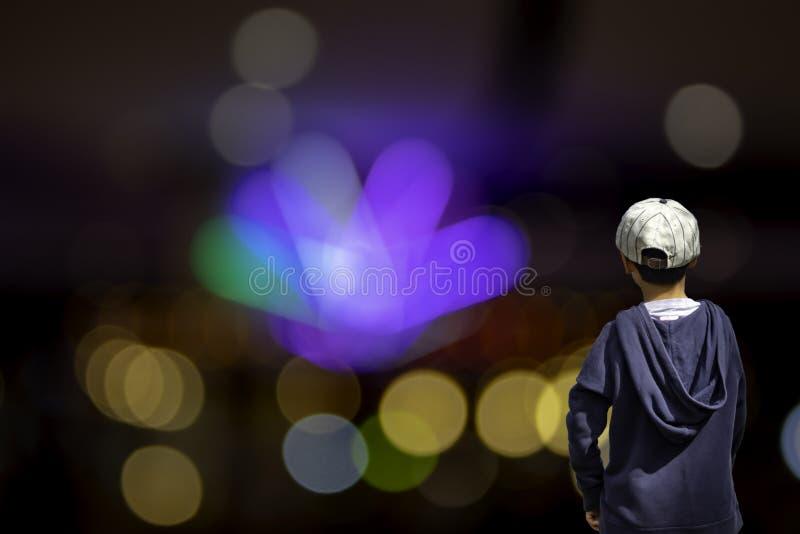 El muchacho asiático ve las luces borrosas de la luz de la casa y de calle, bergantín foto de archivo
