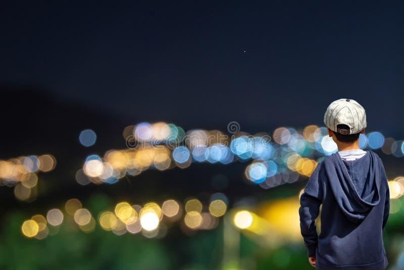 El muchacho asiático ve las luces borrosas de los hogares en la montaña imagen de archivo libre de regalías