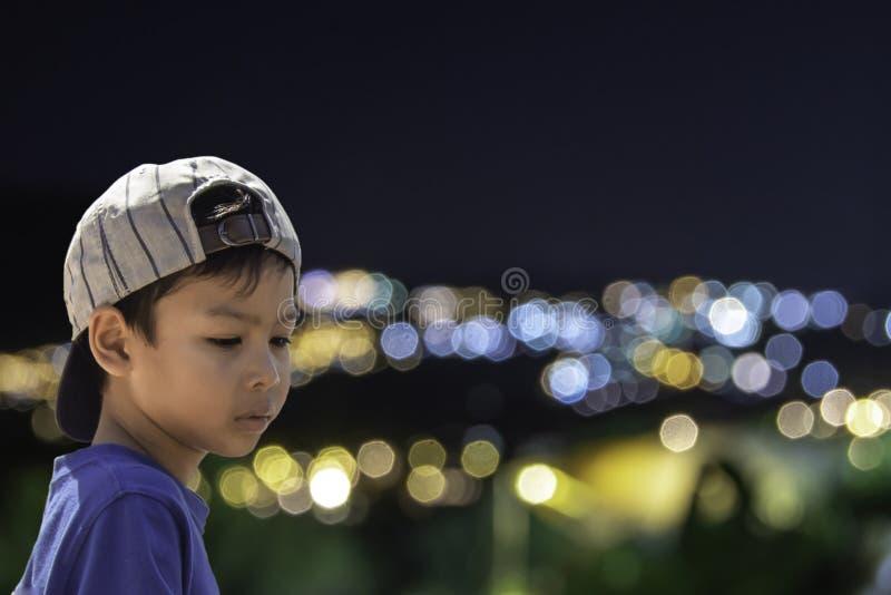 El muchacho asiático ve las luces borrosas de los hogares en la montaña foto de archivo