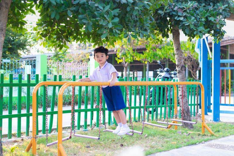 El muchacho asi?tico cuelga la barra de mono o la barra de la balanza para la balanza en el patio al aire libre foto de archivo libre de regalías