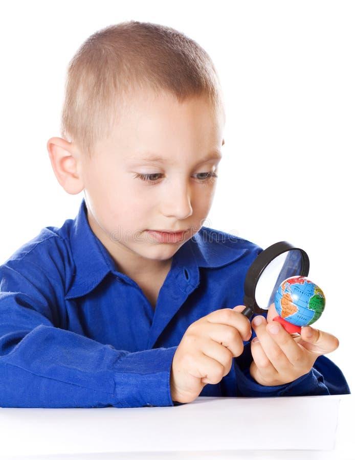 El muchacho atento examina el globo fotografía de archivo libre de regalías
