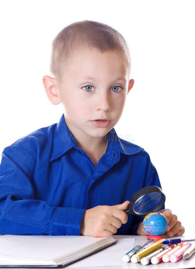 El muchacho atento examina el globo imágenes de archivo libres de regalías