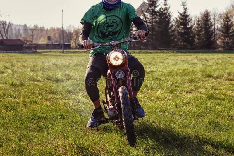 El muchacho atolondrado joven monta a un pionero pasado de moda rojo de Jawa 50 de la moto Esta motocicleta del veterano fue util fotografía de archivo