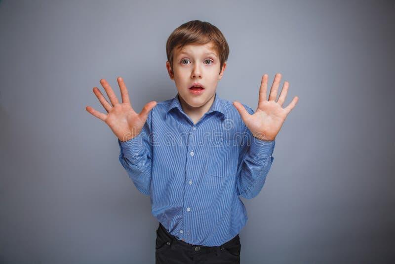 El muchacho aumentó sus manos, palmas hacia fuera imagenes de archivo