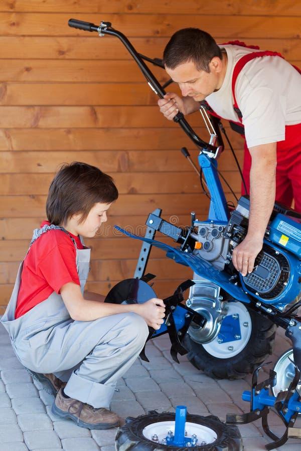El muchacho ayuda a su padre que monta una máquina del cultivador fotografía de archivo