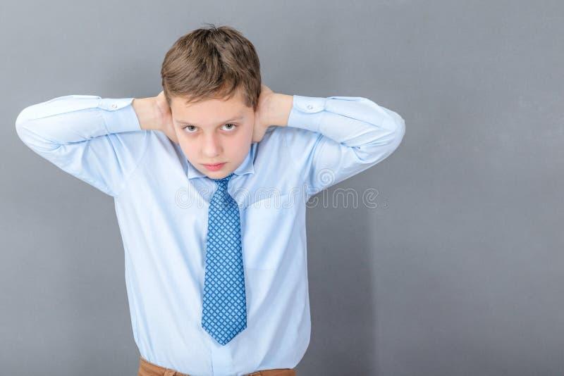 El muchacho bajo tensión se cierra los oídos imagen de archivo libre de regalías
