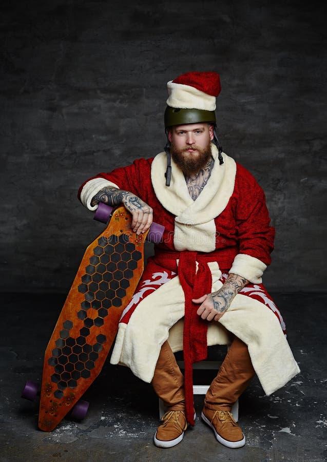 El muchacho barbudo del patinador en el ` s de Papá Noel viste fotografía de archivo
