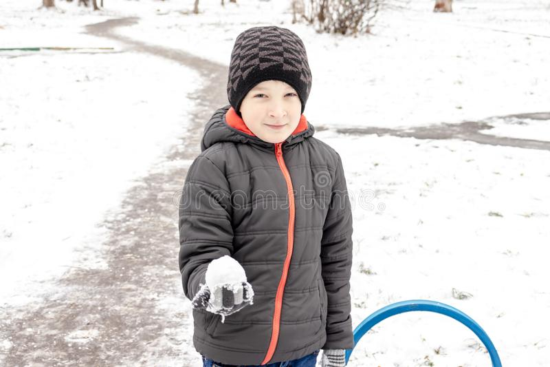 El muchacho caucásico esculpe las bolas de nieve, actividades al aire libre del invierno, concepto de los deportes imagenes de archivo