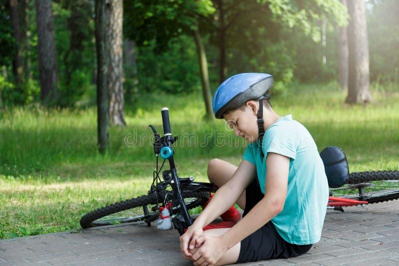El muchacho caucásico joven en casco y la camiseta blanca consiguió accidente y se sienta en la tierra después de caer de la bici foto de archivo libre de regalías