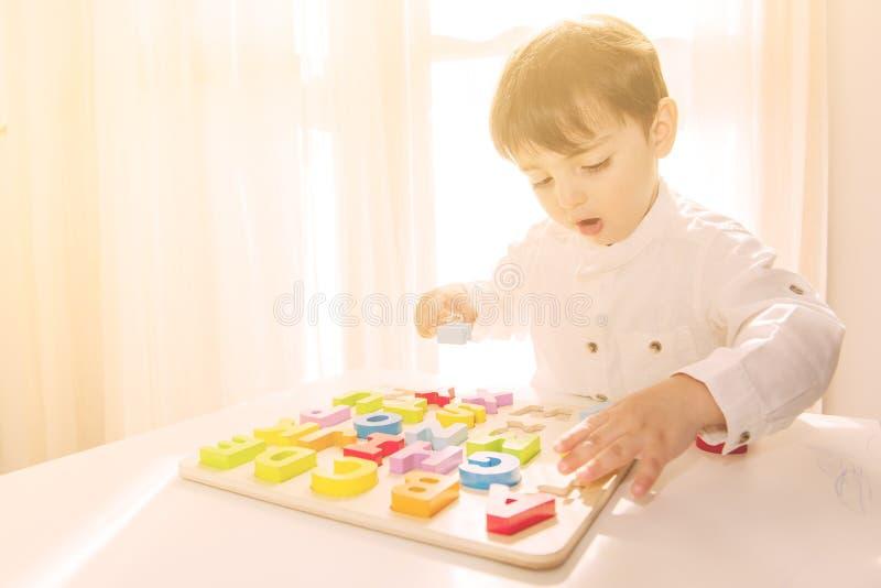 El muchacho caucásico joven juega con las letras de madera coloridas fotos de archivo libres de regalías