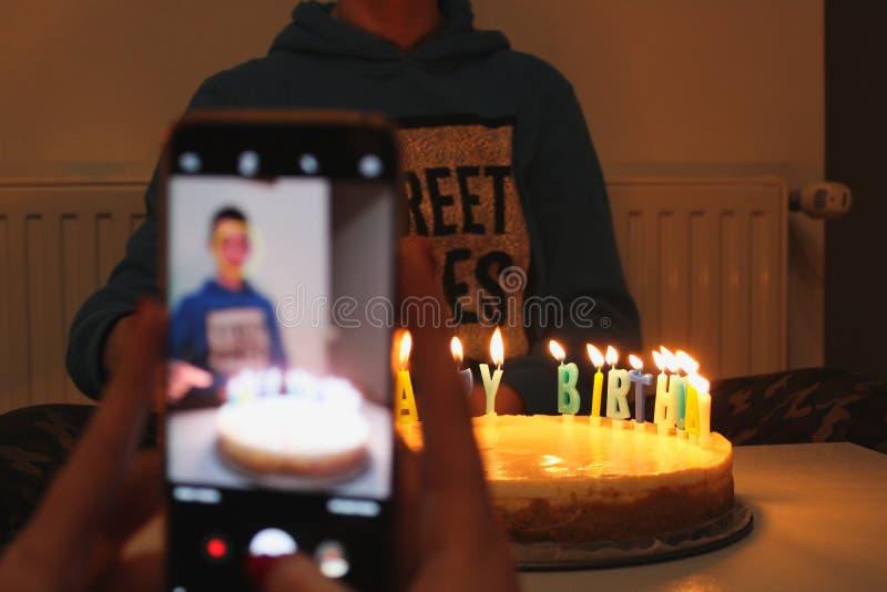 El muchacho celebra cumpleaños con la torta de cumpleaños blanca con las velas coloridas, visión a través de la pantalla del móvi imagen de archivo libre de regalías