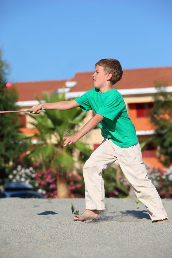 El muchacho coge la raqueta de tenis de la bola en la playa imágenes de archivo libres de regalías