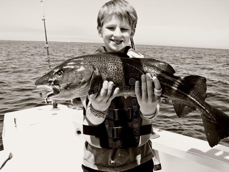 El muchacho coge pescados fotos de archivo