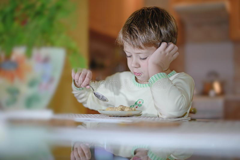 El muchacho come en la tabla imagenes de archivo
