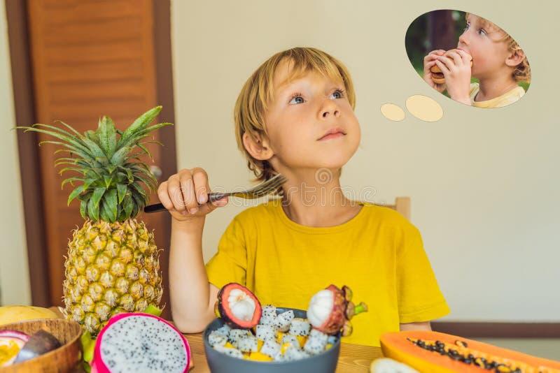 El muchacho come la fruta pero sueños sobre la hamburguesa Comida dañina y sana para los niños Niño que come el bocado sano veget fotos de archivo
