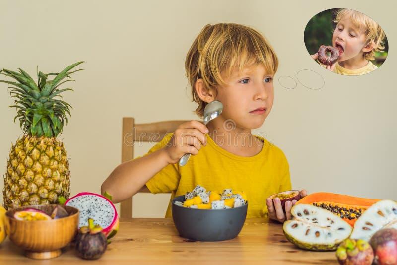 El muchacho come la fruta pero sueños sobre los anillos de espuma Comida dañina y sana para los niños Niño que come el bocado san fotos de archivo