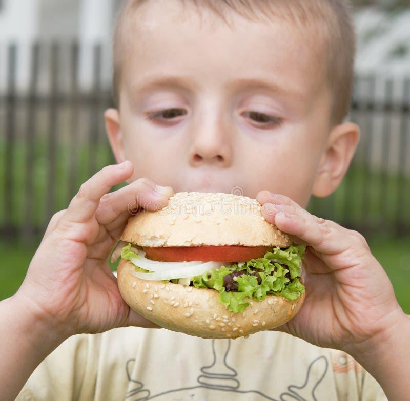El muchacho come la hamburguesa fotografía de archivo libre de regalías