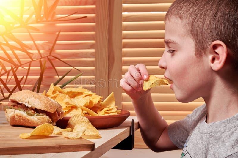El muchacho come las patatas fritas deliciosas en café El niño sostiene los microprocesadores en su mano y los trae a su boca Ali foto de archivo