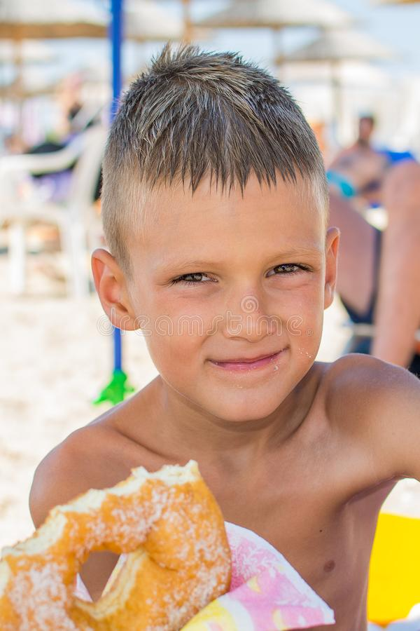 El muchacho come un buñuelo en la playa foto de archivo libre de regalías
