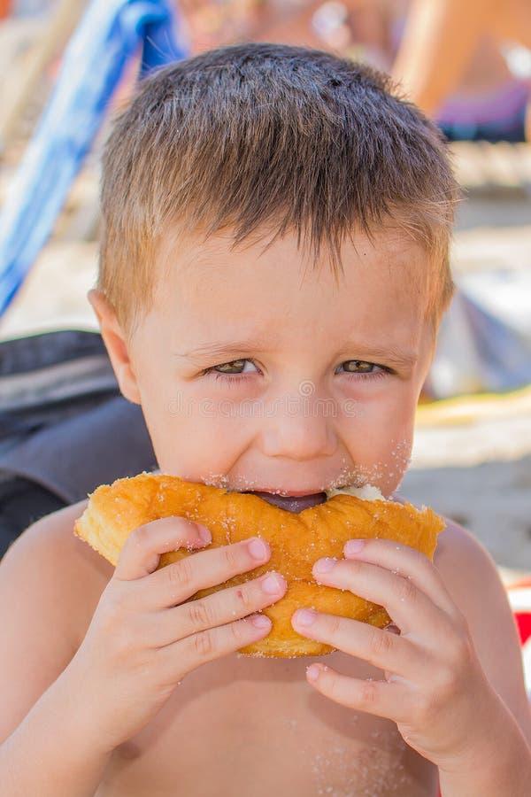 El muchacho come un buñuelo en la playa fotos de archivo