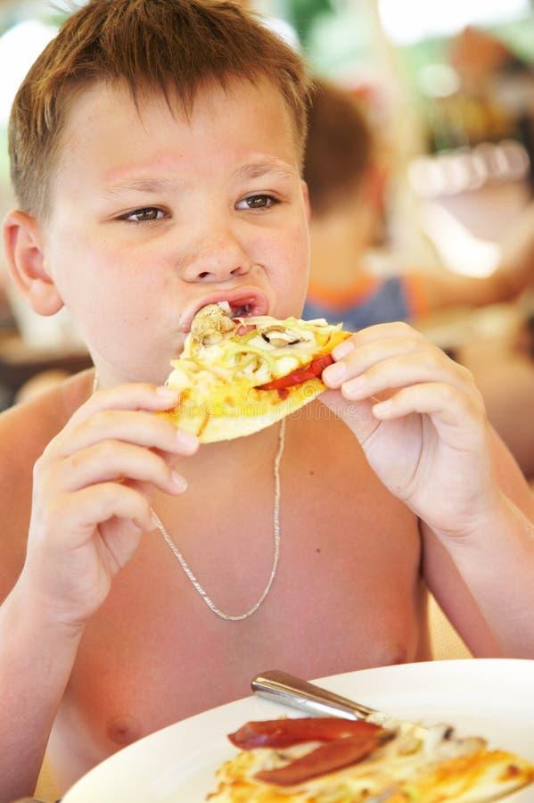El muchacho come una pizza en café del verano en una playa imagen de archivo libre de regalías