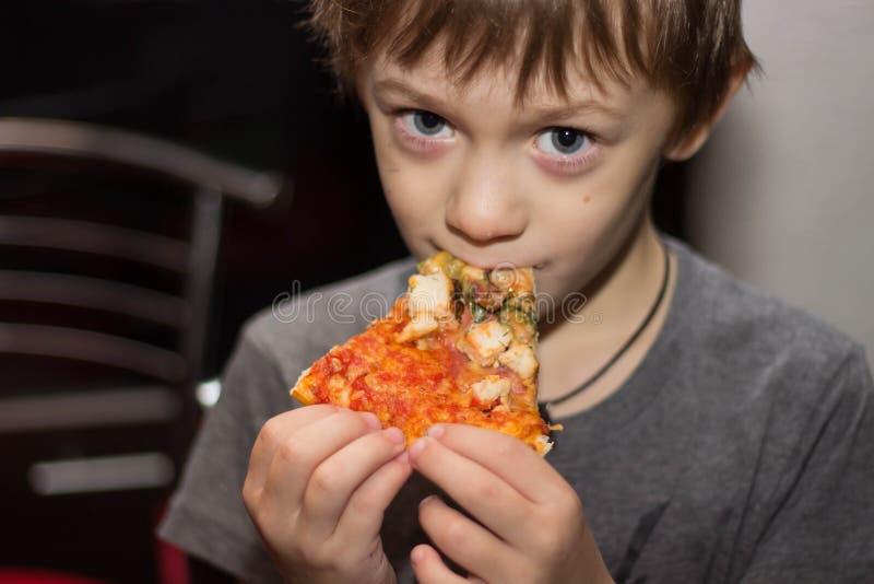 El muchacho come una pizza muy sabrosa con gran placer imágenes de archivo libres de regalías